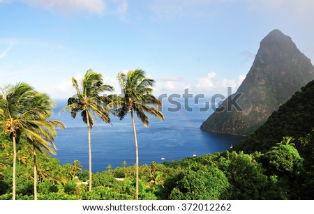 Rainbow begins to form over the blue water in Piton's Bay - stock photo