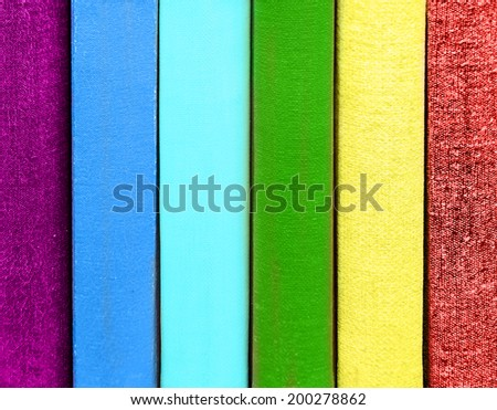 Rainbow books in library shelf - stock photo