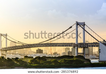 Rainbow bridge located at Odaiba with Tokyo tower in the background - stock photo