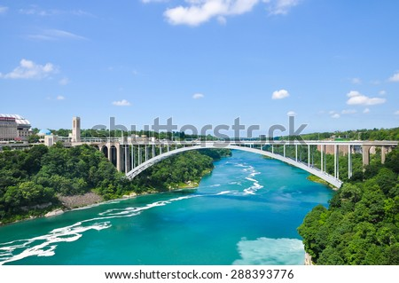 Rainbow Bridge over river with blue sky - stock photo
