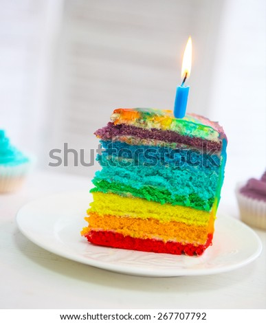 Rainbow cake decorated with birthday candle on the Birthday table - stock photo