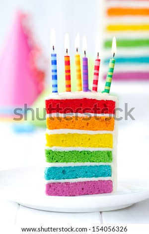 Rainbow cake decorated with birthday candles - stock photo
