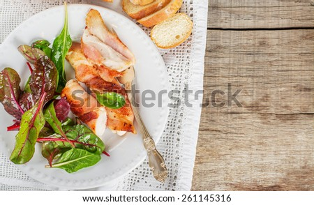rainbow chard salad in bowl with chicken fillet, fried in bacon. - stock photo