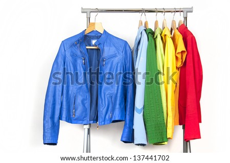 Rainbow clothes on wooden hangers, isolated on white. - stock photo