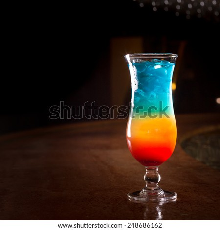 Rainbow cocktail on the bar stand with dark background. Shallow DOF