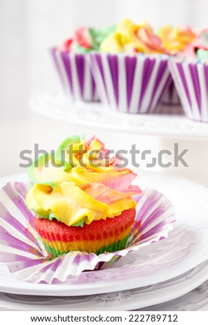Rainbow colored muffins ready to eat - stock photo