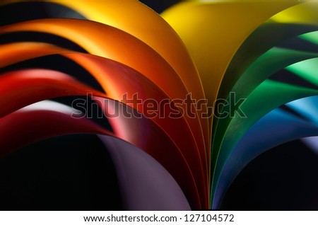 Rainbow colored paper on black background - stock photo