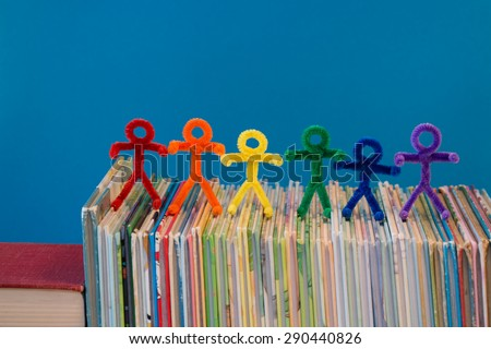 Rainbow colors in pipe-cleaner people. The people/children are all lined up on a pile of books. This is a great photo to help teach educational ideas and concepts to people around the world. - stock photo