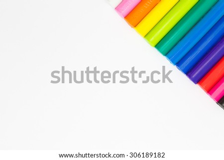 Rainbow colour modelling clay sticks on corner of white background