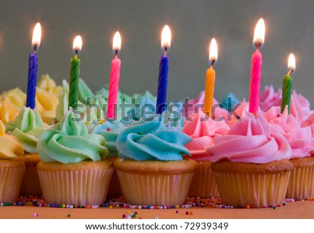 rainbow cupcakes with lit birthday candles - stock photo
