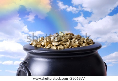 Rainbow Ending at the Proverbial Pot of Gold - stock photo