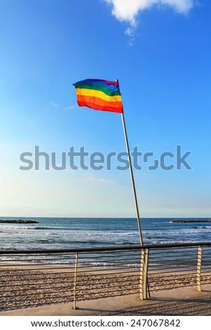 Rainbow gay pride flag on Mediterranean sea free beach, Tel Aviv, Israel - stock photo