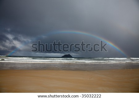 Rainbow in a gale sky over ocean - stock photo