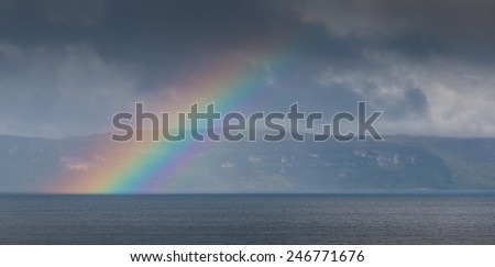 Rainbow in front of the Isle of Skye, Scotland, viewed from the mainland around Applecross village - stock photo