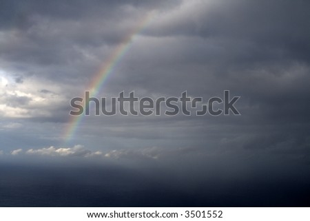 Rainbow in heavy clouds over the sea - stock photo