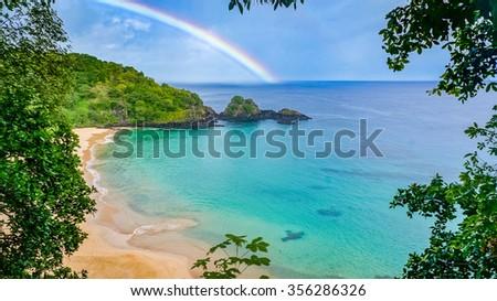 Rainbow in Praia do Sancho beach in Fernando de Noronha, Brazil - stock photo