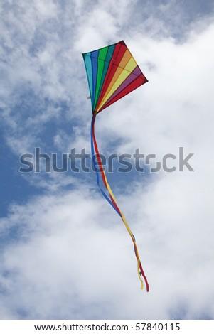 Rainbow kite flying against a blue sky Cornwall, England. - stock photo