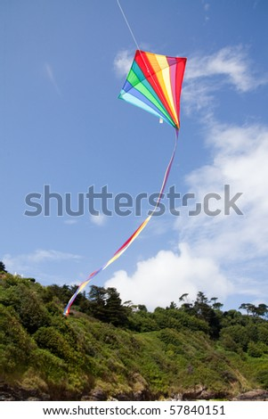 Rainbow kite flying against a blue sky Cornwall, England.