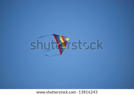 Rainbow kite flying in blue sky