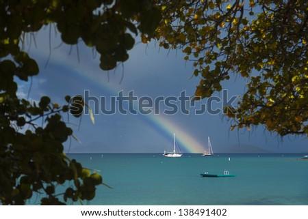 Rainbow landing behind a sailboat, St. John, USVI. - stock photo