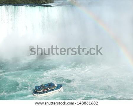Rainbow near tourist boat at Niagara Falls  - stock photo