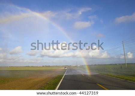 Rainbow on the road with beautiful cloudscape background - stock photo