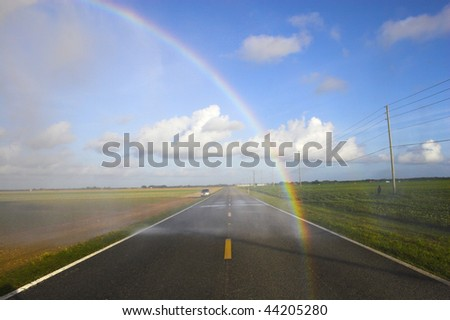 Rainbow on the road with beautiful cloudscape background