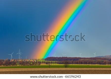 Rainbow over field - stock photo