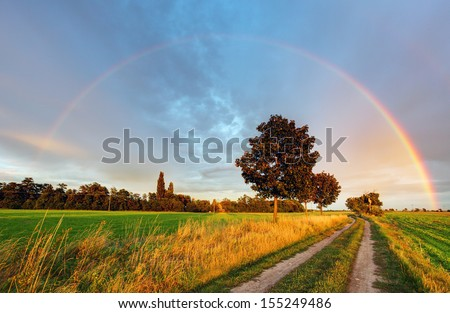 Rainbow over field road - stock photo