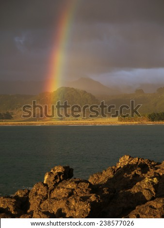 Rainbow over Hicks Bay, New Zealand - stock photo