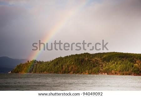 Rainbow over Hood Canal, WA - stock photo