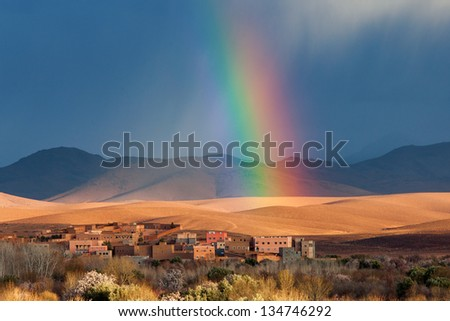 Rainbow over Morocco village in desert - stock photo