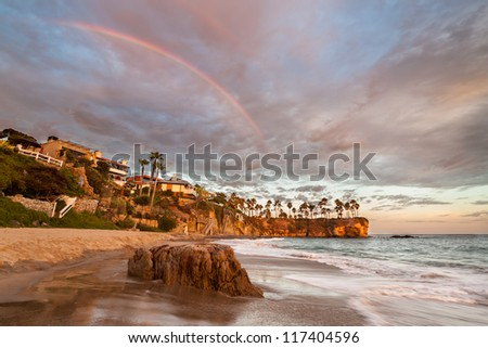 Rainbow over Southern Californian Beach. This is an image taken at sunset of a rainbow over Crescent Bay, Laguna Beach, Southern California. - stock photo