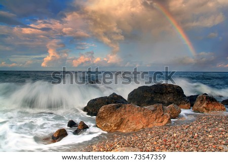 Rainbow over stormy sea - stock photo