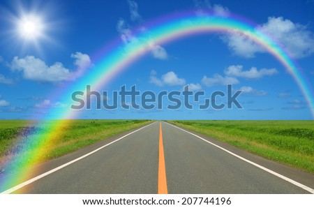 Rainbow over straight road - stock photo