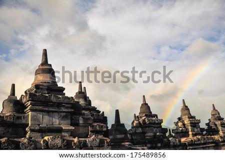 Rainbow over Stupa Buddist temple Borobudur complex in Yogjakarta in Java, indonesia - stock photo