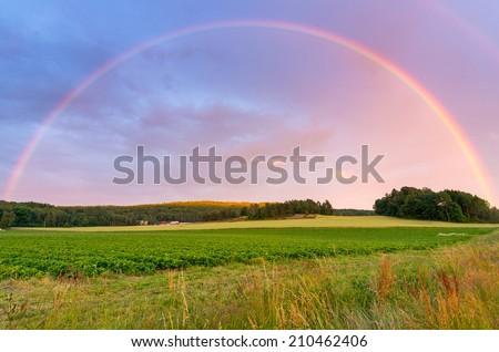 Rainbow over Swedish farm field - stock photo
