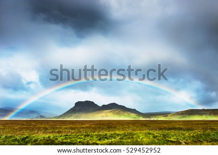 Rainbow over the mountains, South Iceland. Summer landscape
