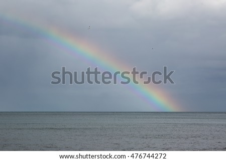 Rainbow over the sea with storm clouds