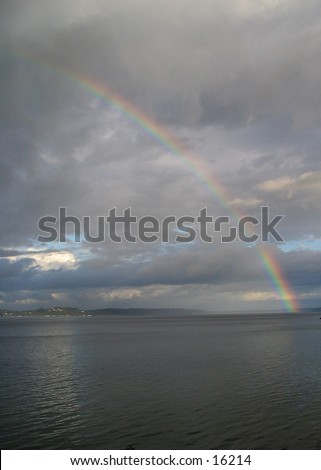 Rainbow over the southern end of Puget Sound, taken from Home (Lakebay), Washington, looking southeast towards Mount Rainier, which is hidden behid the clouds in the center. Portrait orientation.