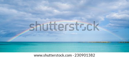 Rainbow over tropical ocean - stock photo