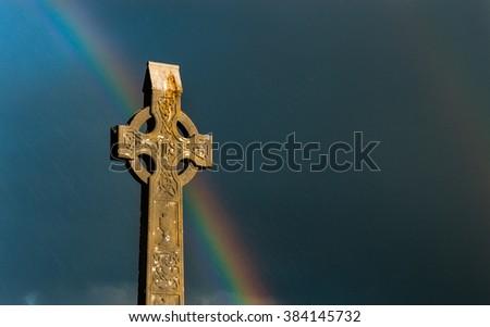 Rainbow sky behind celtic cross gravestone at sunset - stock photo