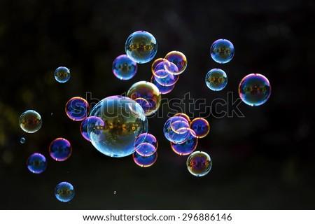 Rainbow soap bubbles on a dark background. - stock photo