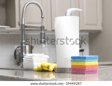rainbow sponges, paper towels, gloves in modern kitchen for housework - focus on front sponge - stock photo