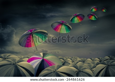 rainbow umbrella in the mass of black umbrellas - stock photo
