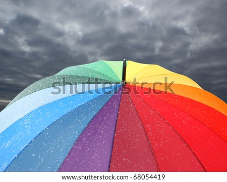 Rainbow umbrella with snowflakes on dramatic sky background - stock photo