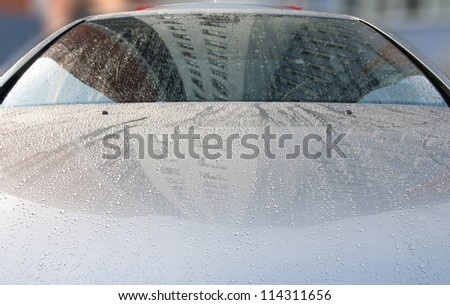 Raindrops on a car surface. The image appears grainy because of the metallic paint. - stock photo