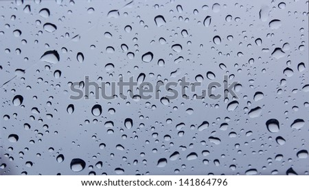 Raindrops on a car windscreen against a cloudy sky in early winter  would be ideal for an abstract wallpaper design. - stock photo