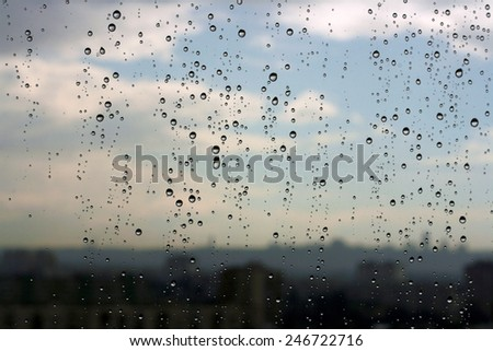 Raindrops on a window against a skyline of the city - stock photo