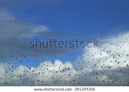 Raindrops on a window pane against a blue sky with clouds